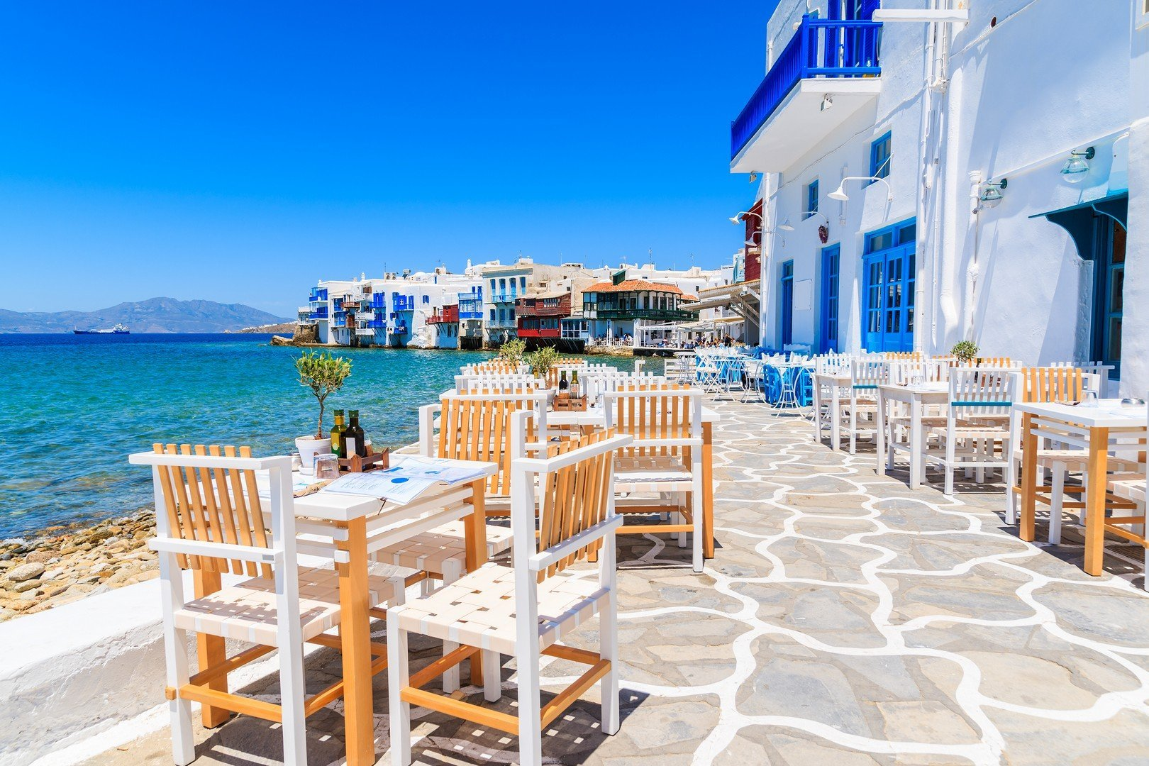 Chairs with tables in typical Greek tavern in Little Venice part of Mykonos town, Mykonos island, Greece - Imagen shutterstock_428874820