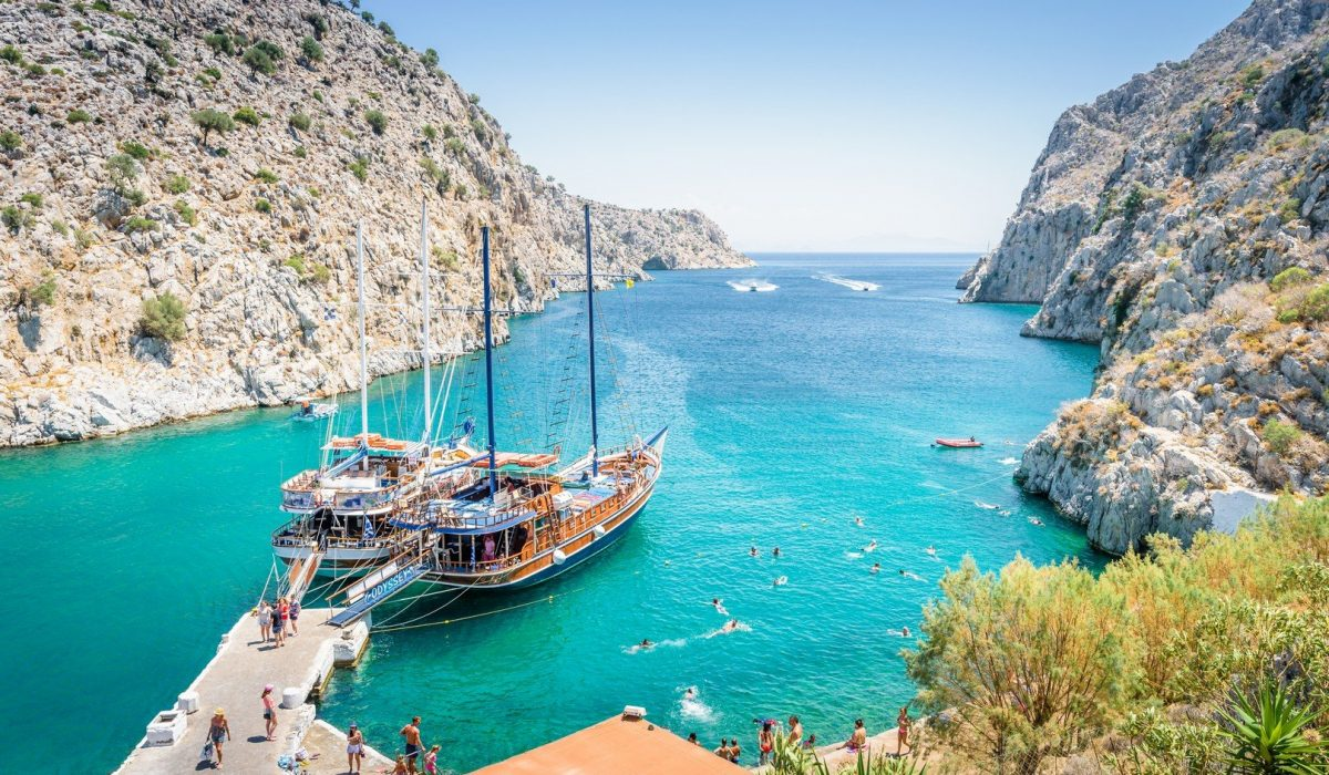 Beautiful sunny coast view to the greek blue sea with crystal clear water beach with big tourist boat cruising around pier in Vathys Bay shutterstock_1036255993