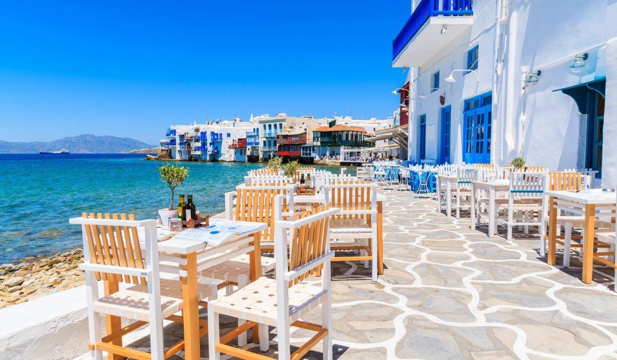 Chairs with tables in typical Greek tavern in Little Venice part of Mykonos town, Mykonos island, Greece - Imagen shutterstock_428874820