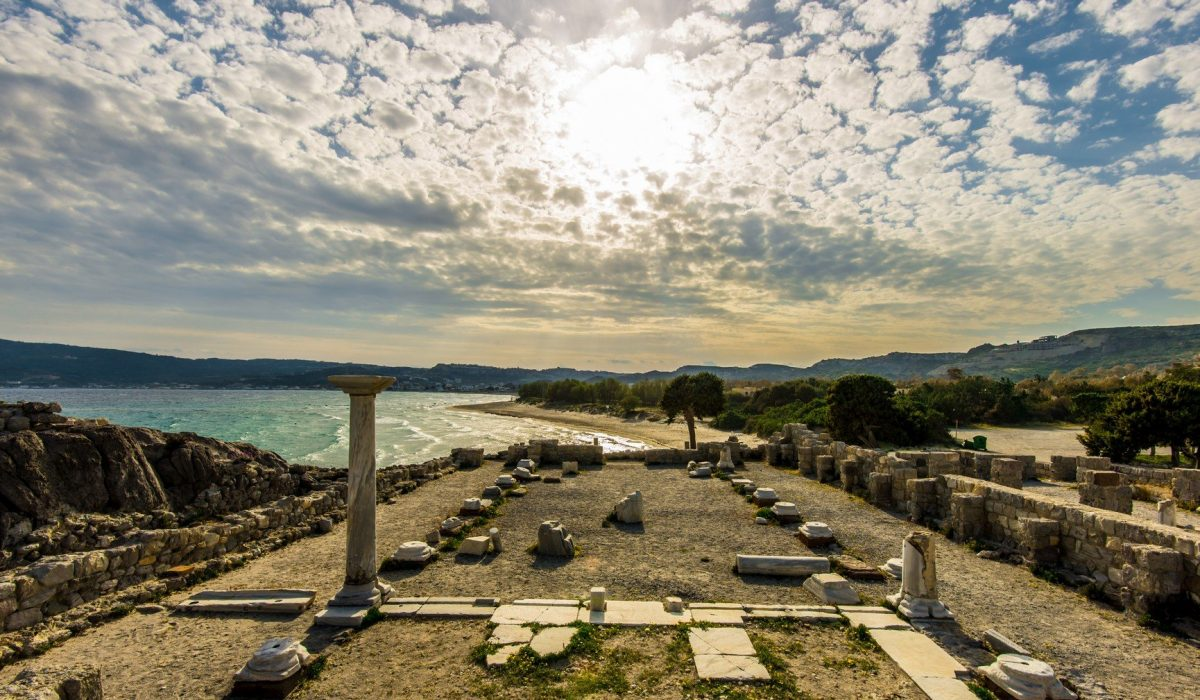 landscape of old ruins of ancient greece in Kos, with the sun on the top center of the picture and the sea and clouds in the background - Imagen shutterstock_368813348